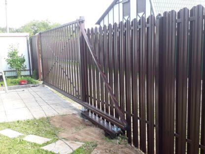Фасад забора из коричневого евроштакетника с откатными воротами в г. Ступино